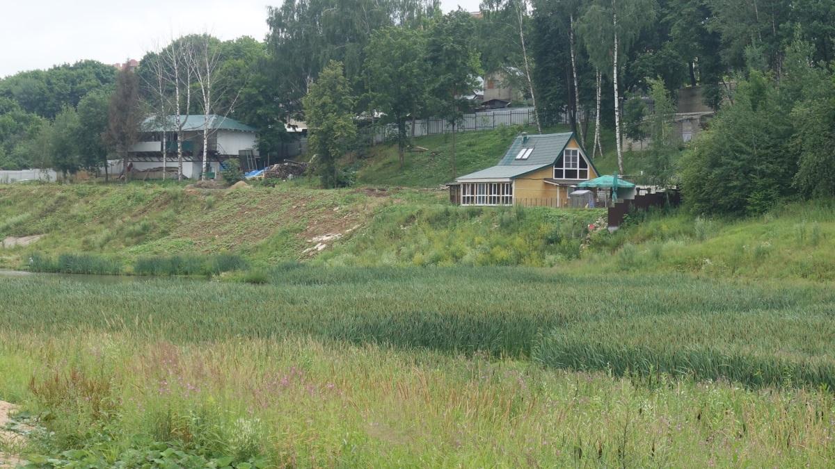 Ближе к плотине появляется мелкая гладь воды и здание бывшего кафе